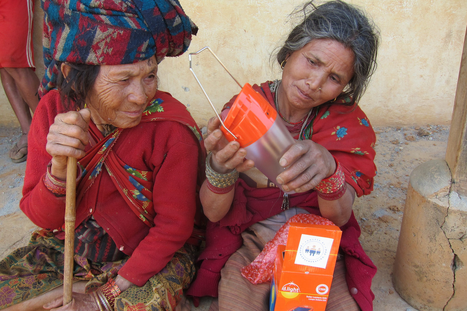 Two women inspect the d.light S20 solar lantern in Dhading.