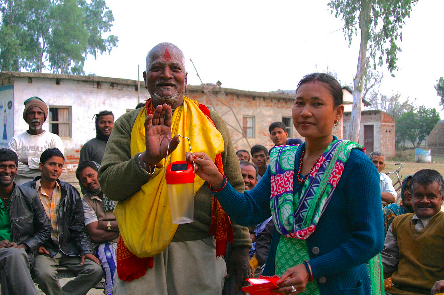 Entrepreneur Lalita Chaudhary stands with a new happy solar customer.